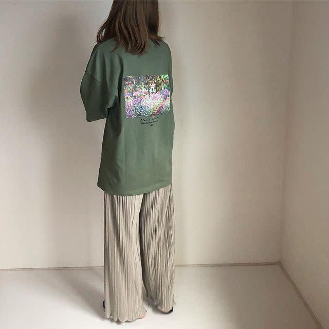 オーバーサイズTシャツにプリーツパンツを履いた女性