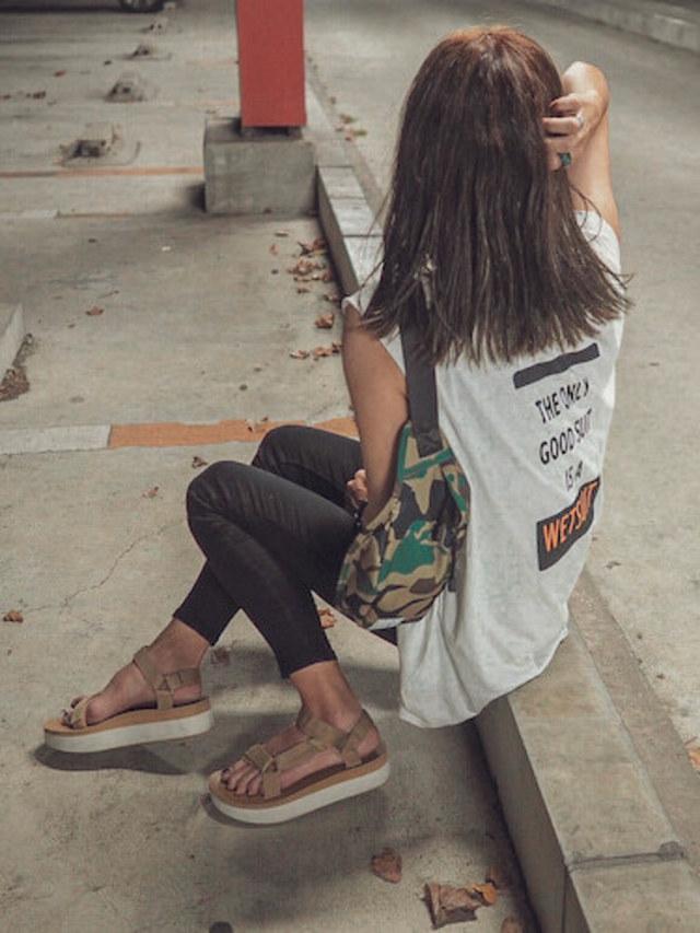 白のバックロゴTシャツに迷彩のウエストバッグを合わせている女性