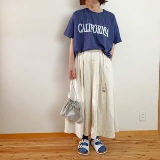 チノスカートとTシャツのコーデにガチャベルトをしている女性