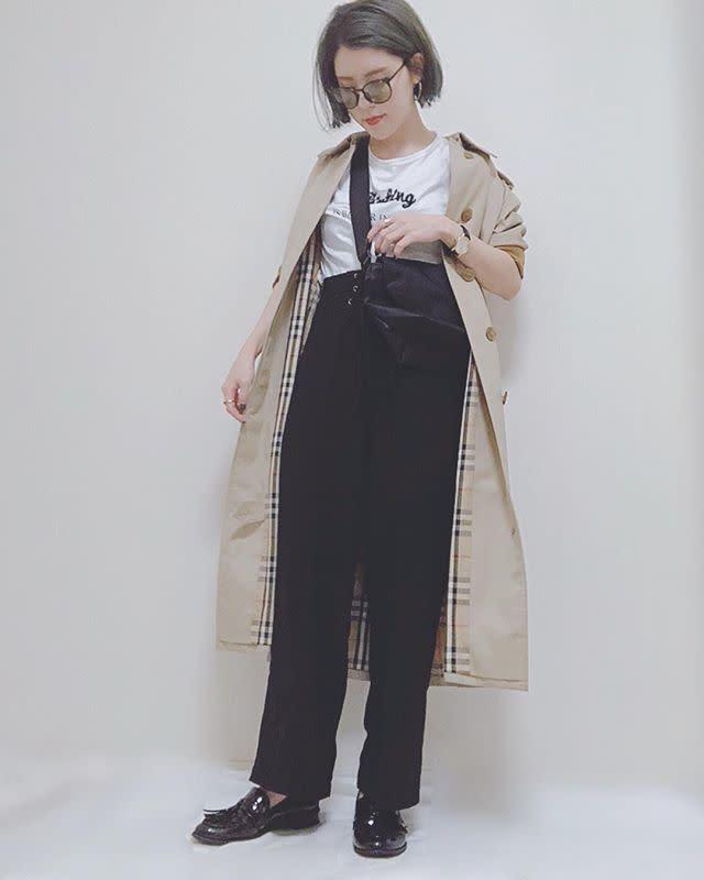 トレンチコートと黒のパンツを着用した女性