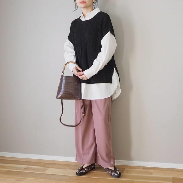シャツとベストとピンんくのワイドパンツを着用した女性