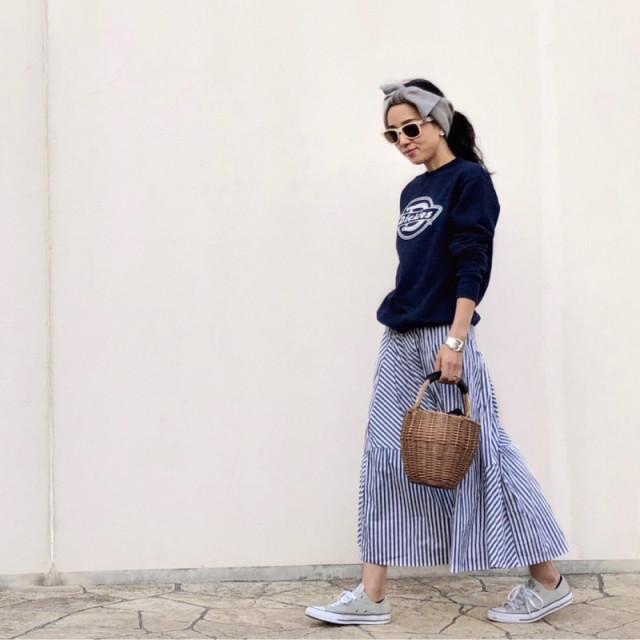 スウェットとストライプのスカートを着用した女性