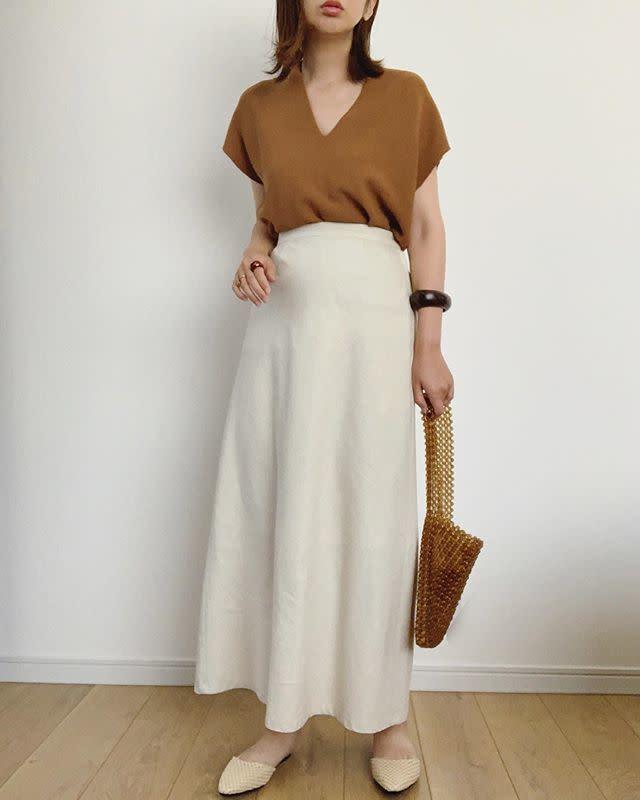 ブラウンのトップスにホワイトリネンスカートを履いた女性