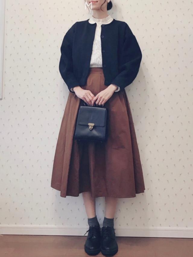 ブラウンのフレアスカートと黒アウターを合わせて、オックスフォードシューズを履いている女性