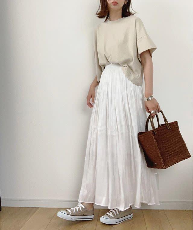 ベージュのTシャツと白のスカートを着用した女性