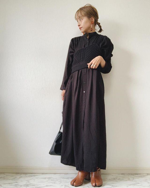 黒のワンピースとビスチェを着用した女性