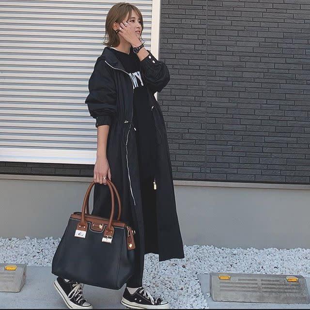 ロングコートとロゴスウェットを着用した女性