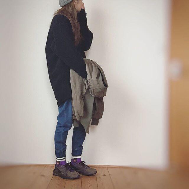 黒トップスにネイビーのジョガーパンツに紫の靴下を合わせている女性