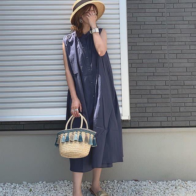 ノースリワンピとカゴバックを着用した女性