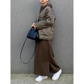 ブラウンダウンジャケットにブラウンワンピースを着た女性