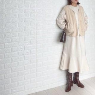 アイボリーのボアベストと白のスウェットワンピースにブラウンロングブーツを履いた女性