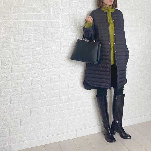 黒ダウンジャケットとグリーンニットに黒ロングブーツを履いた女性