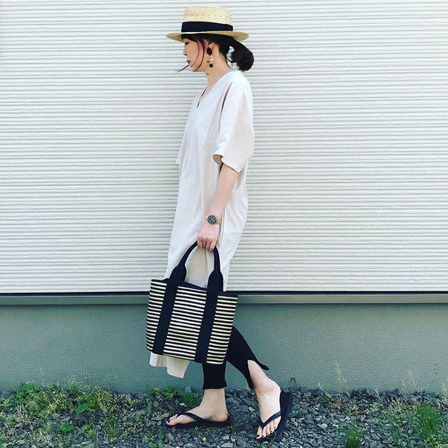 白のシャツワンピースと黒のレギンスの組み合わせにカンカン帽とボーダー柄バッグを合わせたコーディネート