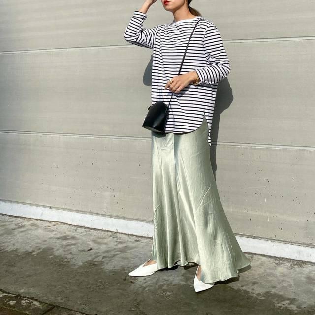 ボーダーカットソーとサテンスカートを着用した女性