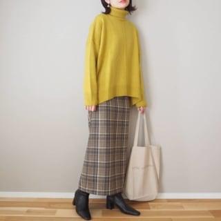 黄色ニットにチェック柄タイトスカートを履いた女性