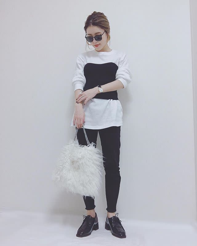 白のプルオーバーに黒スキニーを履いた女性