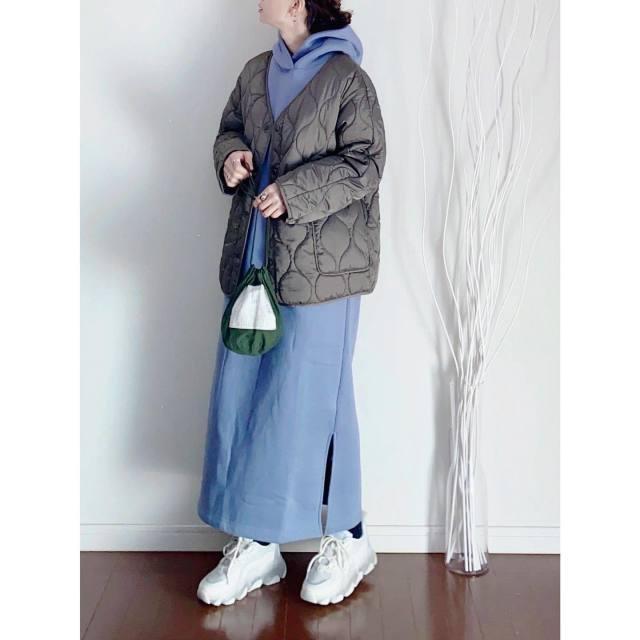 キルティングブルゾンとフーディーワンピースを着用した女性