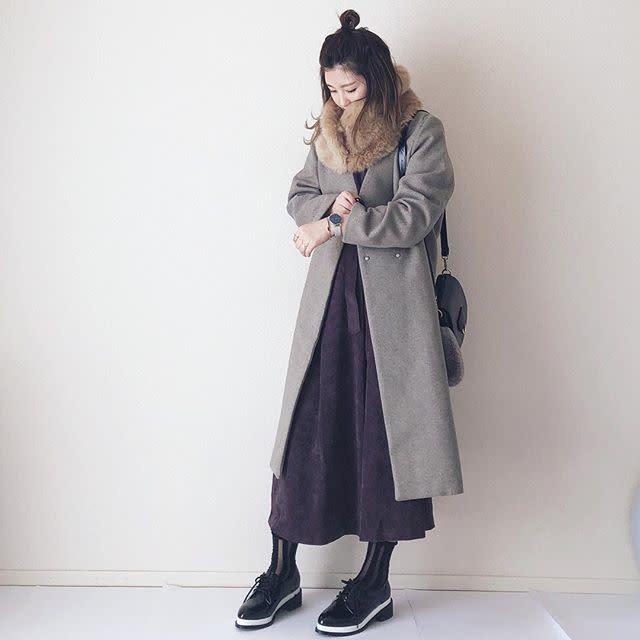 グレーコートにパープルワンピースを着た女性