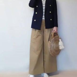 黒ジャケットとボーダートップスにベージュワイドパンツを履いた女性
