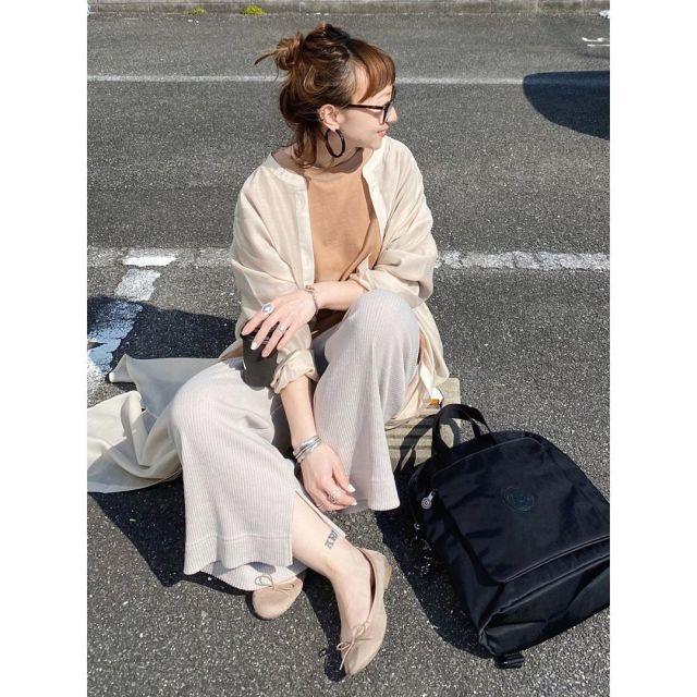 ベージュのガウンとワイドパンツを着用した女性