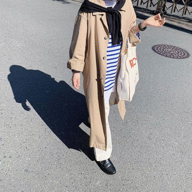 トレンチコートとボーダーカットソーを着用した女性