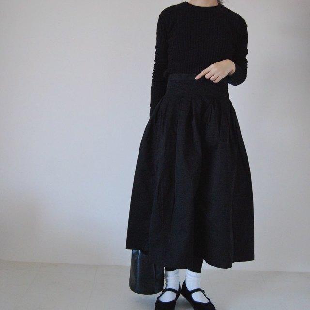 黒トップスとフレアスカートを着用した女性