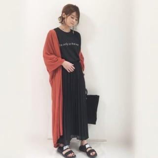 ブラックプリーツスカートにオレンジのロングカーデ女性