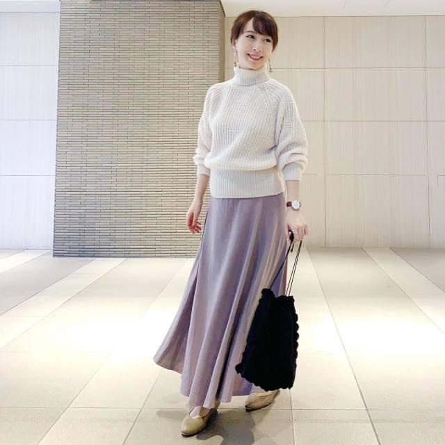 ローゲージのタートルニットにピンクのスカートを履いている女性