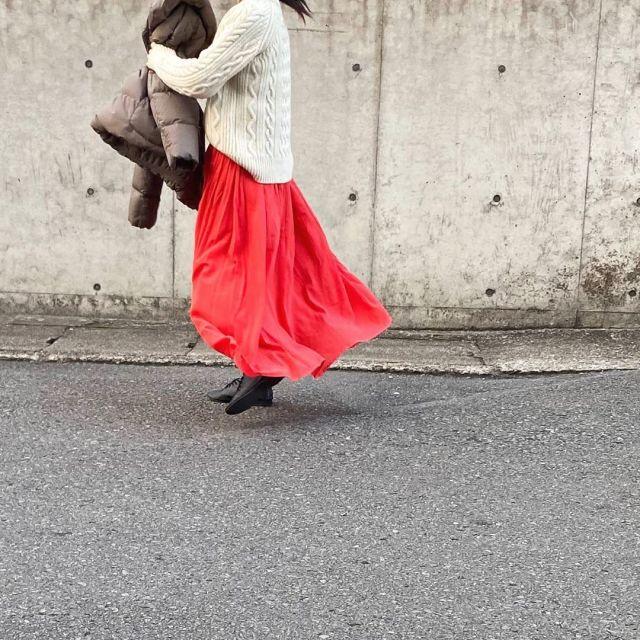 ブラウンダウンジャケットと白ニットに赤マキシスカートを履いた女性