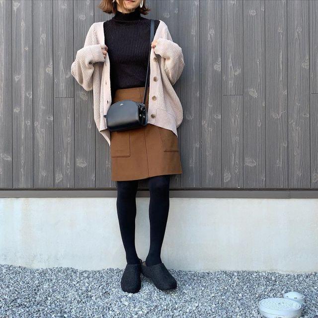 ベージュカーディガンと黒タートルネックニットにブラウンタイトミニスカートを履いた女性