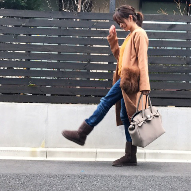 ブラウンファーコートにデニムパンツとムートンブーツを履いた女性