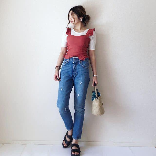 白のTシャツに赤のフレアタンクトップのレイヤードとブルージーンズの組み合わせに黒のサンダルのコーディネート