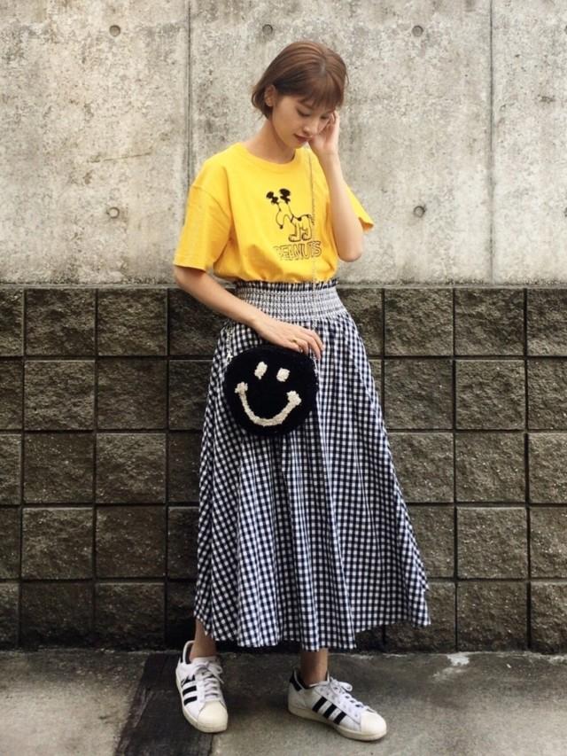 黄色のスヌーピーTシャツにギンガムチェックのフレアスカートと白のスニーカーを合わせたコーディネート