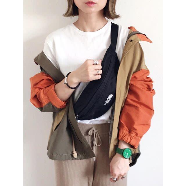 ベージュとオレンジのカラーブロックのマウンテンパーカーを着用した女性