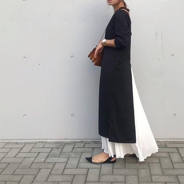 黒のワンピースと白のプリーツスカートを着用した女性