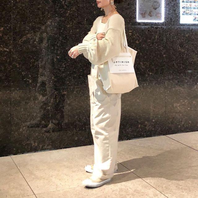 白のニットとサロペットを着用した女性