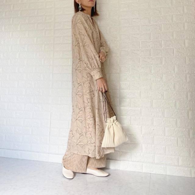 ベージュの花柄ロングワンピを着た女性
