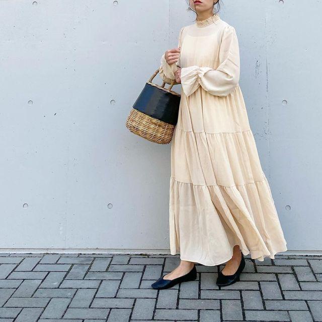 ベージュのティアードワンピースを着用した女性