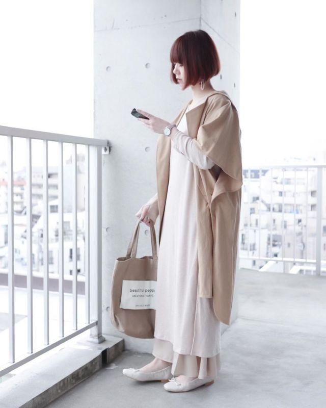 変形コートとTシャツワンピースを着用した女性
