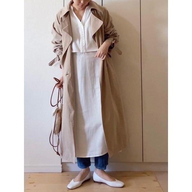 ベージュのコートに白のワンピースとデニムのコーデ