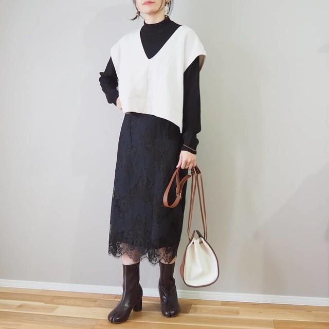 黒の長袖ワンピースに白のブイネックショートニットベストと黒のショートブーツを合わせたコーディネート