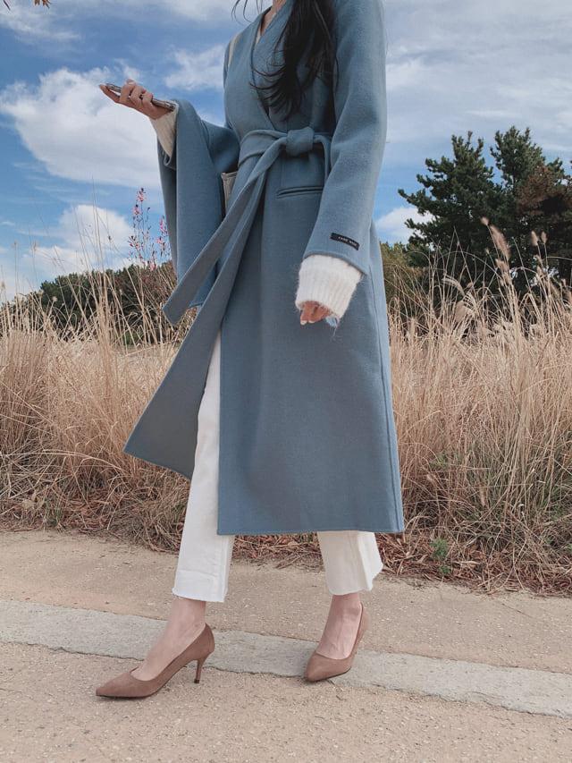 Vネックのノーカラーガウンコートを着た女性
