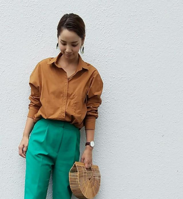 バンブーバッグを持ち、ブラウンのシャツとグリーンのパンツを合わせている女性
