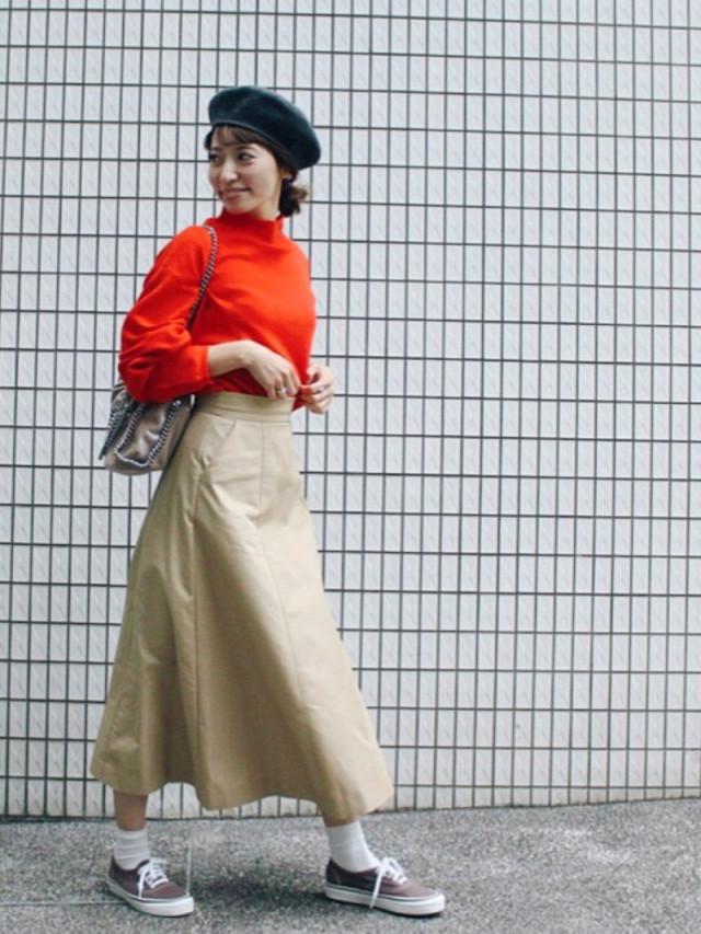オレンジのニットとベージュのスカートを着用した女性
