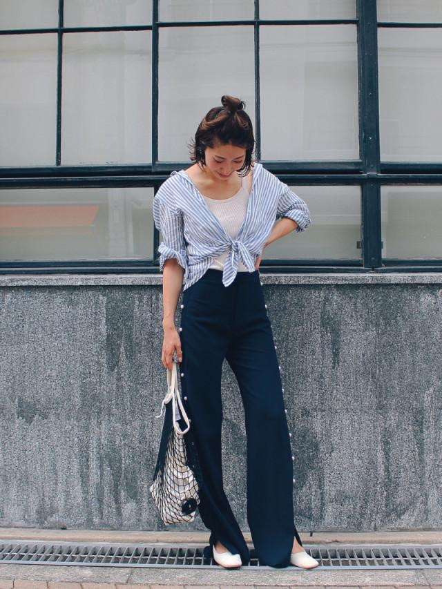 ストライプのシャツと黒パンツを着用した女性
