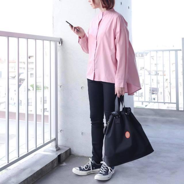 ピンクのシャツにブラックパンツを合わせている女性
