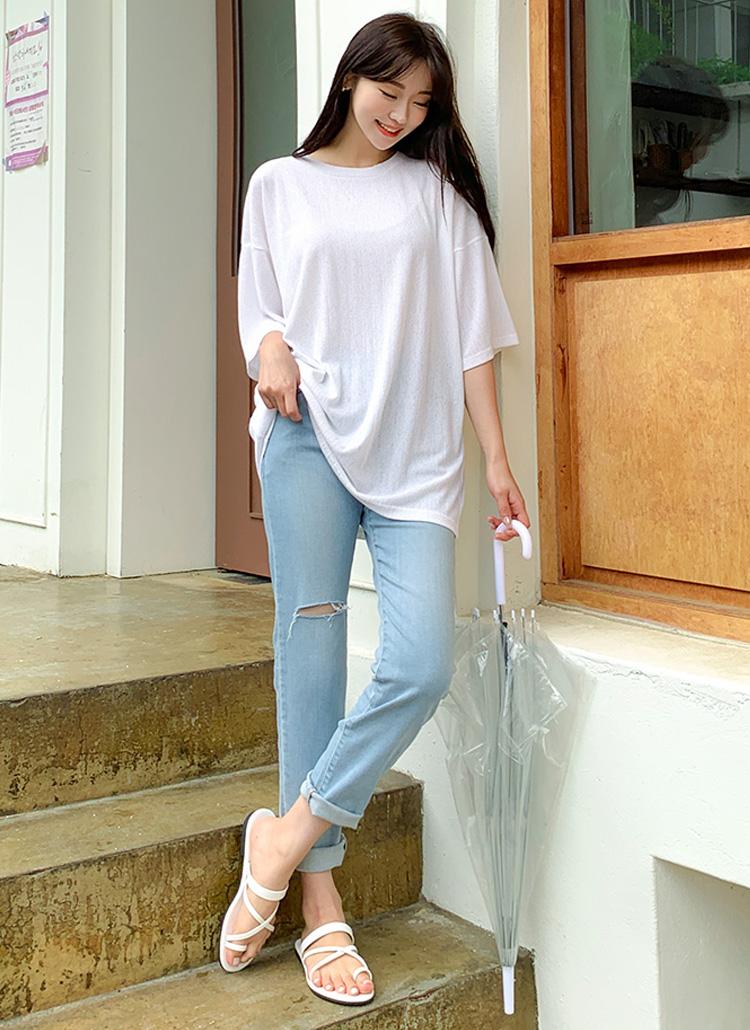 ドロップショルダーのTシャツにデニムパンツを合わせている女性