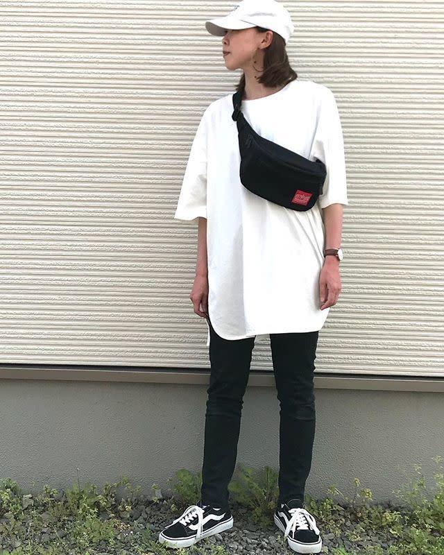 ホワイトビッグTシャツに黒スキニーパンツ、ホワイトキャップ、バンズの黒いオールドスクールの女性