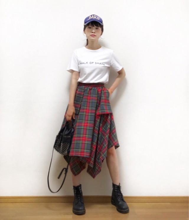 白ロゴTシャツにレッドチェックの変型スカート、マーチンの8ホールブーツの女性