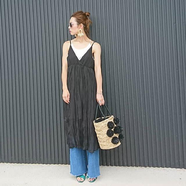 黒のキャミワンピースとデニムを着用した女性